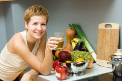 Glass of juice. Beautiful woman with glass of juice and fresh fruits in the kitchen Stock Photography