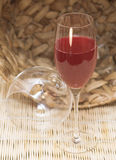 Glass with juice. Grape juice in a glass. A glass standing against a wattled basket Royalty Free Stock Photography