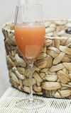 Glass with juice. Juice in a glass. A glass standing against a wattled basket Royalty Free Stock Photos