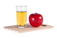 Glass of juice and apple. Glass of fresh juice and red apple on cutting board Stock Image