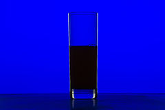 Glass with juice with blue background Royalty Free Stock Photos