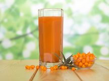 A glass of juice, bowl of sea buckthorn berries, individual berr Stock Image