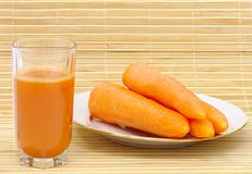 Glass with   juice and carrot on plate. Fresh neat juice and carrot on plate on bamboo napkin Stock Image