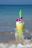 Glass Of Juice Cocktail Washed By Waves. Glass Of Juice Cocktail With Two Straws Washed By Waves On The Beach Stock Image