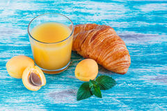 Glass of juice, croissant and apricots Royalty Free Stock Images