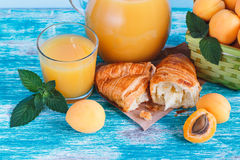 Glass of juice, croissant and apricots Royalty Free Stock Photography