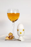 A glass of juice and an egg. Still-life wiht an egg, a glass of juice and a flower Stock Images