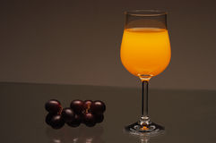 Glass of juice with grapes. Black grapes and a glass of orange juice on a glass table Stock Photos