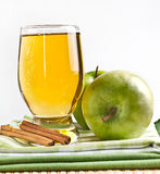 Glass of juice and green apple with cinnamon Stock Image