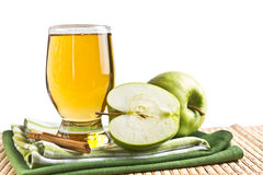 Glass of juice and green apple with cinnamon Stock Images