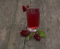 Glass of juice and red currant on the old desktop Stock Photos