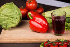 Glass of juice, red pepper and fresh vegetables Royalty Free Stock Images