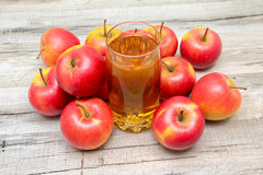 Glass of juice and ripe apples on a wooden background Royalty Free Stock Photos