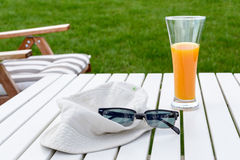 Glass of juice with a summer hat and sunglasses. On the table Stock Images