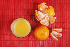 Glass of juice and tangerine Stock Photos