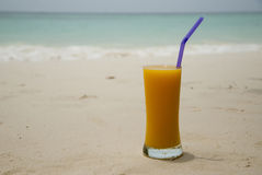 Glass with juice on the tropical beach with a sea and sand as a Royalty Free Stock Photography