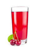 Glass juice and two ripe juicy cherries with green leaf Royalty Free Stock Images