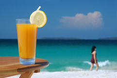Glass of Juice and Walking Woman. Against Tropical Sea royalty free stock image
