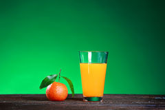 Glass of juise and ripe sweet tangerine with leaf on green. Tangerines with leaves on wooden surface. Citrus fruit Royalty Free Stock Photos