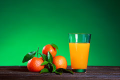 Glass of juise and ripe sweet tangerine with leaf on green. Tangerines with leaves on wooden surface. Citrus fruit Royalty Free Stock Images