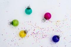Glass julgarnering ser igenom med konfettier Fotografering för Bildbyråer