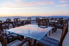Glass kafétabeller på taket av semesterorten med siktshavet och härlig solnedgång royaltyfri foto
