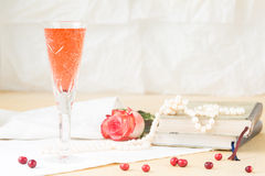 Glass of kir royal cocktail with vintage books and pearls Stock Images