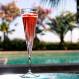 Glass of Kir Royal. On the glass table in outdoor resort bar Stock Images