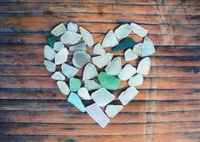 Glass kiselstenhjärta för kust på träbakgrund Sockra den glass mosaiken för dag för valentin` s Royaltyfri Bild