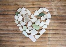Glass kiselstenhjärta för kust på träbakgrund Sockra den glass mosaiken för dag för valentin` s Royaltyfri Foto