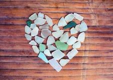 Glass kiselstenhjärta för kust på träbakgrund Sockra den glass mosaiken för dag för valentin` s Royaltyfria Foton