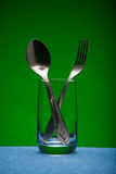 Glass and kitchen devices. On a green background Stock Image