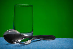 Glass and kitchen devices. On a green background Stock Photo
