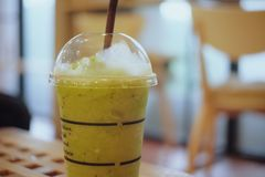 A glass of Kiwi Juice Frappe on the table with blur background. In cafe royalty free stock photo