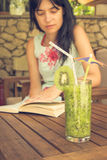 Glass of kiwi smoothie and female reading the book in the backgr Royalty Free Stock Photography