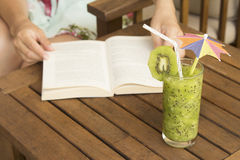 Glass of kiwi smoothie and a hands on opened book Royalty Free Stock Photography