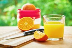 Glass, knife oranges and juicer Stock Photos