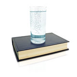Glass of knowledge. A glass full of water with letters and some hidden words on the book Royalty Free Stock Image