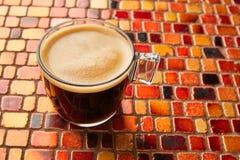 Glass kopp för kaffe med kräm på den röda tabellen för tegelplattor Fotografering för Bildbyråer