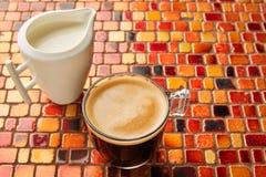 Glass kopp för kaffe med kräm på den röda tabellen för tegelplattor Arkivbild