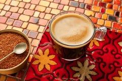 Glass kopp för kaffe med kräm på den röda tabellen för tegelplattor Arkivbilder