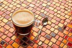 Glass kopp för kaffe med kräm på den röda tabellen för tegelplattor Arkivfoto