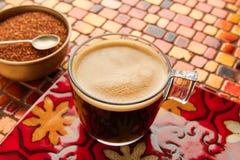 Glass kopp för kaffe med kräm på den röda tabellen för tegelplattor Royaltyfria Bilder