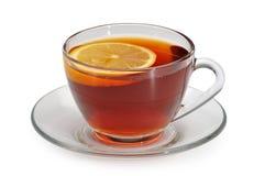 Glass kopp med te och en citron på ett glass tefat Arkivfoto