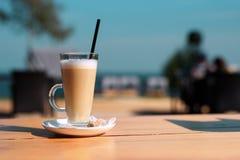 Glass kopp med varma latte och sugrör på en trätabell på sommarterrassen av kafét Arkivfoton