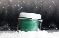 Glass kosmetisk behållare med kräm i snön Royaltyfri Foto