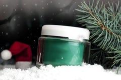 Glass kosmetisk behållare med kräm i snön Arkivbild