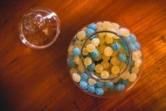 Glass krus av blått- och gulinggodisen royaltyfri foto