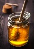 Glass krus av honung på ett träbräde Royaltyfria Bilder