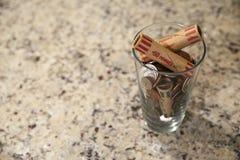 Glass krus av mynt i kopp på kassa för marknad för ändring för rikedom för finans för dollar för bank för skuld för besparingar f arkivfoton